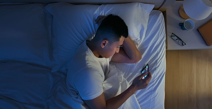 man using mobile in bed