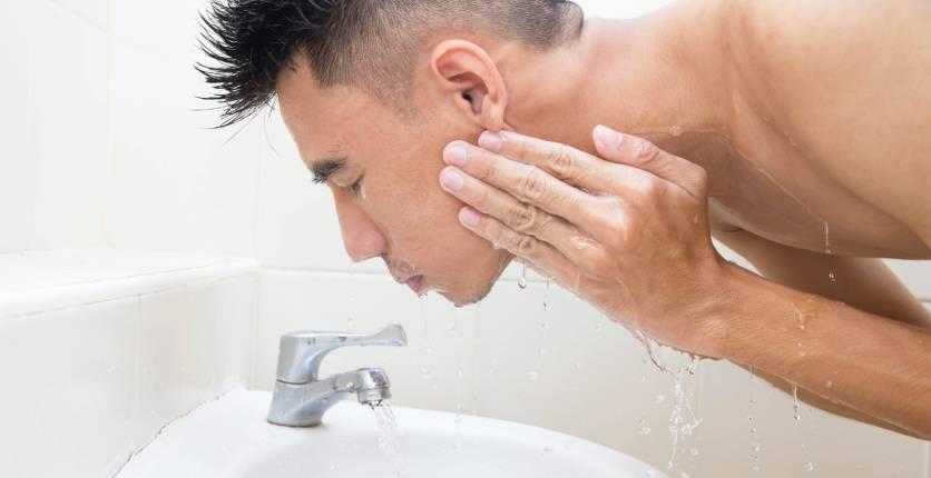man washing face
